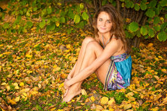 Beautiful woman sitting in the autumn forest Stock Images