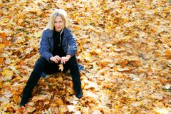 Beautiful woman sitting on autumn leaves Stock Photos