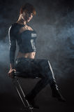 Beautiful woman sitting on a bar stool in profile face Stock Photography
