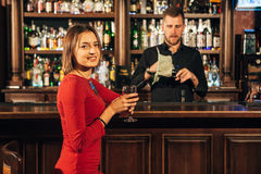Beautiful woman sitting at the bar and waiting for him to mix her cocktail Stock Images