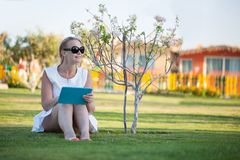 Beautiful woman sitting barefoot on a lawn royalty free stock photo