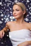 Beautiful woman sitting in bath towel at sauna Royalty Free Stock Images