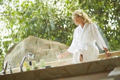 Beautiful woman sitting in bathrobe in bathroom in luxury hotel. stock photos
