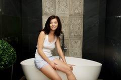Beautiful woman sitting on bathtub. stock photography