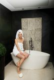 Beautiful woman sitting on bathtub. Royalty Free Stock Images