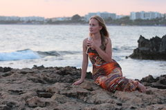 A beautiful woman sitting on the beach and drinking wine. The Mediterranean coast royalty free stock image