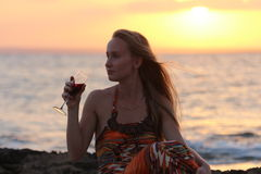 A beautiful woman sitting on the beach and drinking wine. The Mediterranean coast stock photography