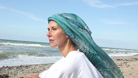 Beautiful woman sitting on the beach and enjoying the sun and wind. Beautiful woman with scarf wrapped around her head sitting on the beach and enjoying the sun stock video footage