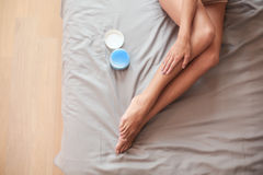 Beautiful woman sitting on bed and applying cream on legs Stock Image
