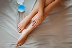 Beautiful woman sitting on bed and applying cream on legs Royalty Free Stock Image