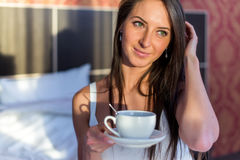 Beautiful woman sitting in bed and drinking coffee or tea the morning stock photo