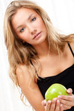 Beautiful woman sitting on bed and holding apple Stock Photo