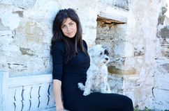 Beautiful woman sitting on a bench with her white dog Stock Photo