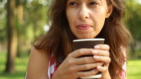 Beautiful woman sitting on a bench in the park and eating a muffin and a latte stock video