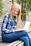 Beautiful woman sitting on bench in park with laptop Royalty Free Stock Photo