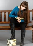Beautiful woman sitting on a bench and reading a book Stock Images