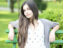 Beautiful woman sitting on bench. Teen  sitting on bench in the park on a summer day Royalty Free Stock Image