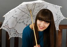 Beautiful woman sitting on a bench with an umbrella in han Stock Photos