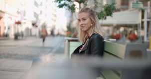 Beautiful woman sitting on bench and waiting for a date. Stock Photo
