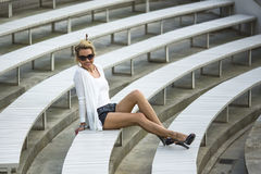 Beautiful  woman sitting on benches in the stadium. Stock Images