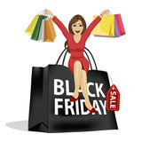 Beautiful woman sitting on big black friday shopping bag Royalty Free Stock Images