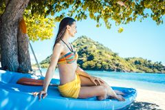 Beautiful woman sitting on boat close to the ocean beach stock photography