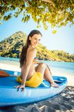 Beautiful woman sitting on boat close to the ocean beach royalty free stock photos