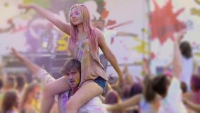 Beautiful woman sitting on boyfriend's shoulders, waving hands at Holi festival