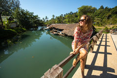 Beautiful woman sitting on the bridge over the river in the asian fishing village. Stock Photography