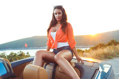 Beautiful woman sitting in cabriolet, enjoying trip on luxury mo Royalty Free Stock Photo