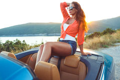 Beautiful woman sitting in cabriolet, enjoying trip on luxury mo Royalty Free Stock Image