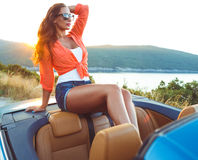 Beautiful woman sitting in cabriolet, enjoying trip on luxury mo Stock Photo