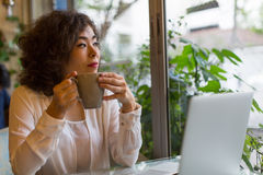 Beautiful  woman sitting in a cafe with a Cup of coffee and a laptop. Royalty Free Stock Image