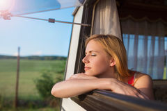 Beautiful woman sitting in a camper van Royalty Free Stock Image
