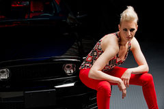 Beautiful woman sitting on a car bumper Royalty Free Stock Photo