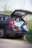 Beautiful woman sitting in the car trunk Stock Photos
