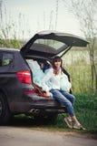 Beautiful woman sitting in the car trunk Stock Photo