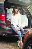 Beautiful woman sitting in the car trunk Royalty Free Stock Photos