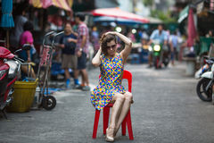 Beautiful woman sitting on a chair in the middle of  street. Royalty Free Stock Photography