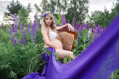 Beautiful woman sitting on a chair surrounded by flowers field. Beautiful young woman in wreath sitting on a chair surrounded by purple flowers field Royalty Free Stock Photography