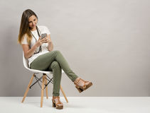 Woman texting. Beautiful woman sitting on a chair and texting a phone message Royalty Free Stock Image