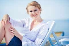 Beautiful woman sitting in chaise Stock Images
