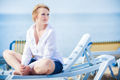 Beautiful woman sitting in chaise Royalty Free Stock Images