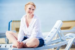 Beautiful woman sitting in chaise Royalty Free Stock Photography