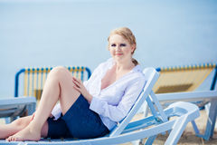 Beautiful woman sitting in chaise Stock Image