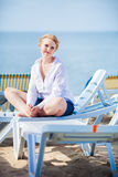 Beautiful woman sitting in chaise Royalty Free Stock Photos