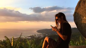 Beautiful Woman Sitting on the Cliff and Texting on Smartphone gadget. Phuket, Thailand. HD slowmotion amazing view. stock video footage