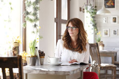 Beautiful woman sitting in coffee shop royalty free stock images