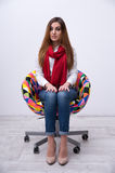 Beautiful woman sitting on the colourful chair Royalty Free Stock Photography
