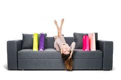 Beautiful woman sitting on couch with many shopping bag around acting joyful and happy with arms spread wide Stock Images